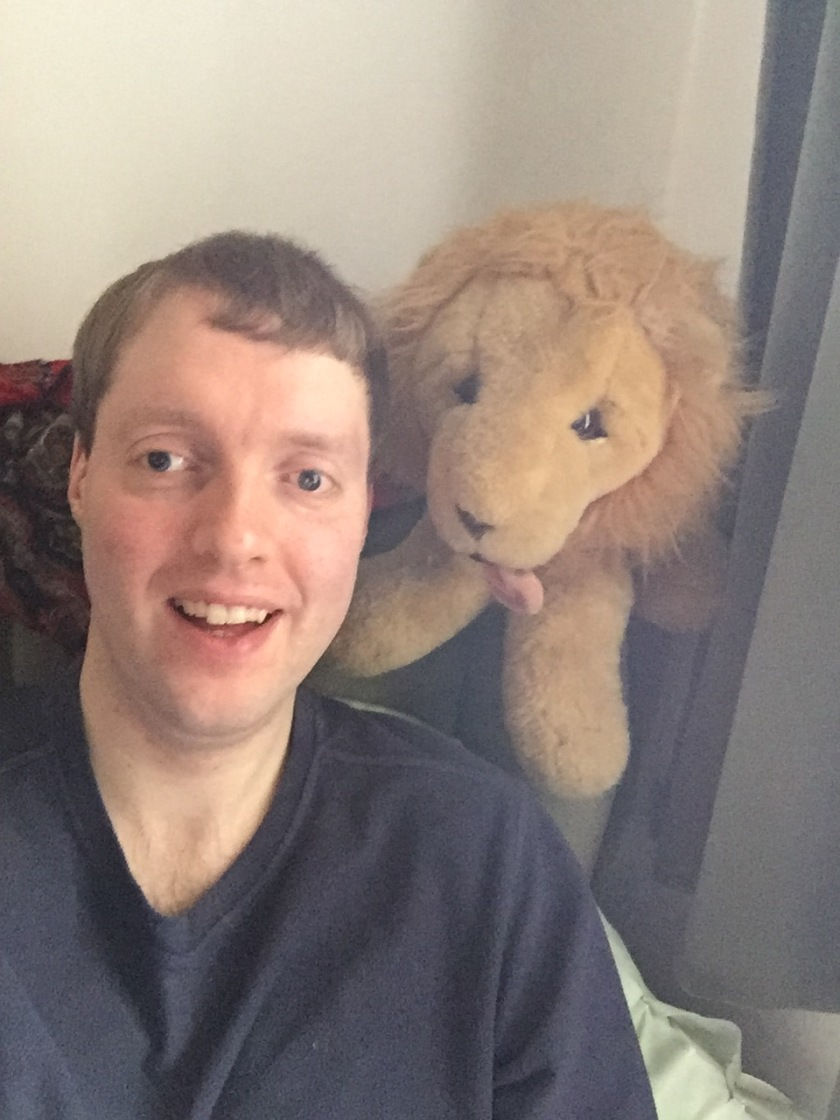 Me sitting in a chair, with a cuddly toy lion sitting on the corner of the back of the chair and looking over my shoulder.
