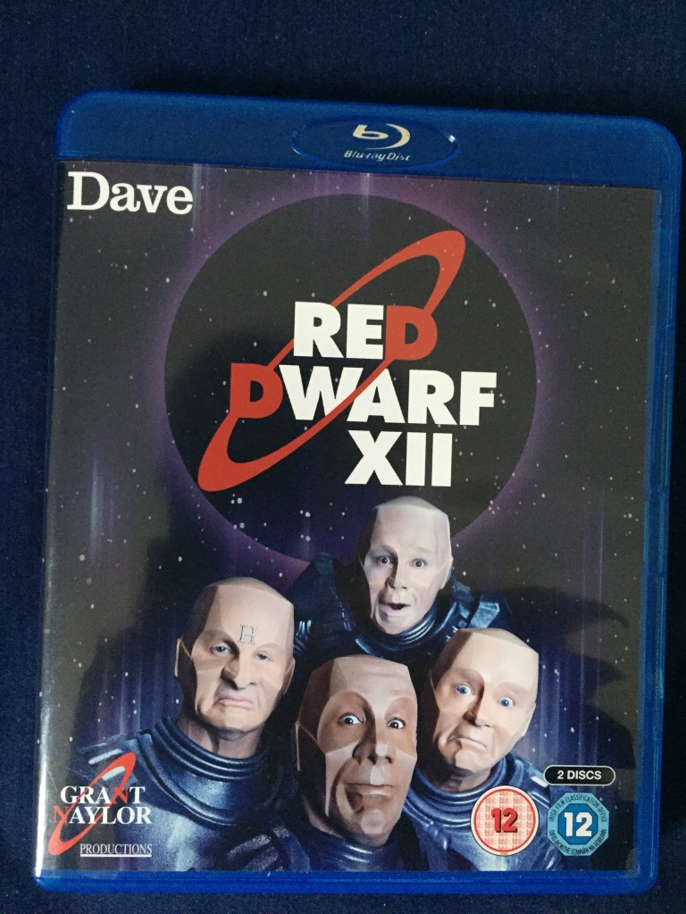 Front of the Blu-ray case for Red Dwarf series 12, showing the 4 members of the crew all in mechanoid form like Kryten.