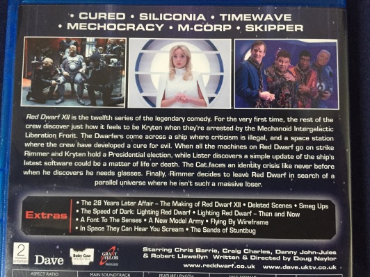 Rear of the Blu-ray case for Red Dwarf series 12, including episode titles, screenshots and a general description of the show, plus a list of extras including a behind-the-scenes documentary and featurettes, deleted scenes and smeg ups.