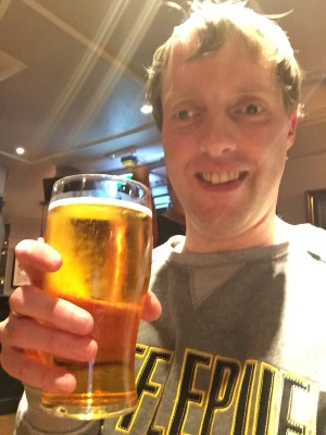 Selfie of me in a pub, smiling and holding a pint of cider.