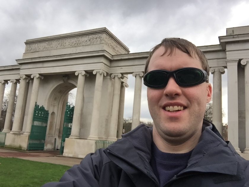 Selfie of me in front of the huge gateway to Hyde Park, consisting of 3 tall archways separated by many stone columns.