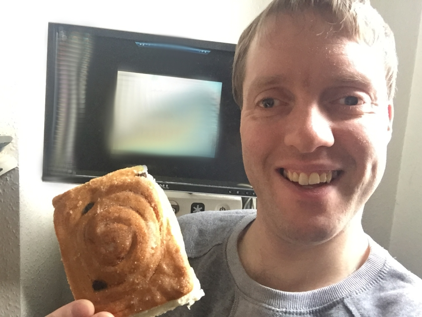 Glen sitting in front of his computer screen, smiling and holding a square cake with a swirly design on top.