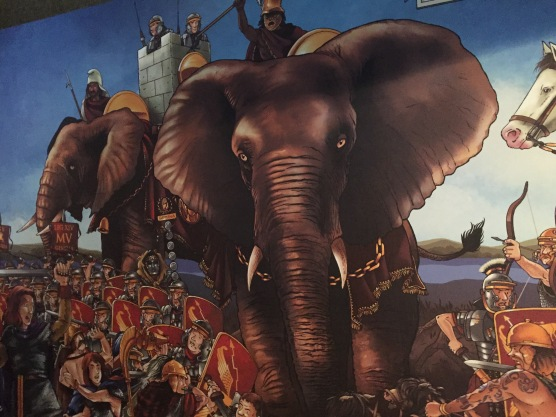 Painting of a Roman soldier riding a huge elephant, surrounded by other Roman soldiers on foot.