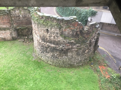 A large round section of the Roman stone wall that used to surround London. now partly in ruins with pieces missing at the top