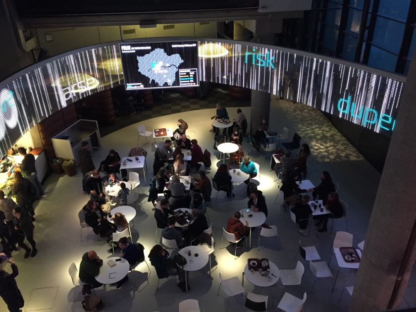 Museum café, with a computer screen stretching around the curved ceiling above. A large monitor in the centre shows a map of London. The screen stretching around the wall has the words risk, dupe and arse in random positions, over a variety of vertical lines.