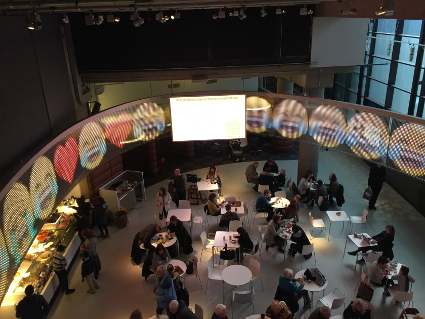 Museum café, with a computer screen stretching around the curved ceiling above, filled with large crying with laughter emojis.