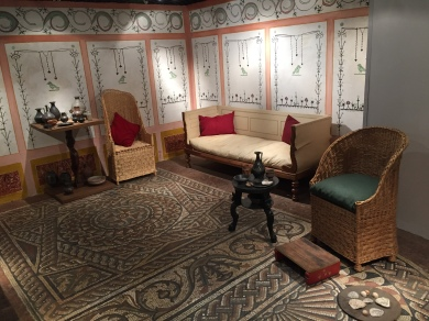 A furnished room containing a white 3 seater sofa, 2 chairs made of a wicker basket type material with tall, rounded backs, and an ornately decorated carpet.