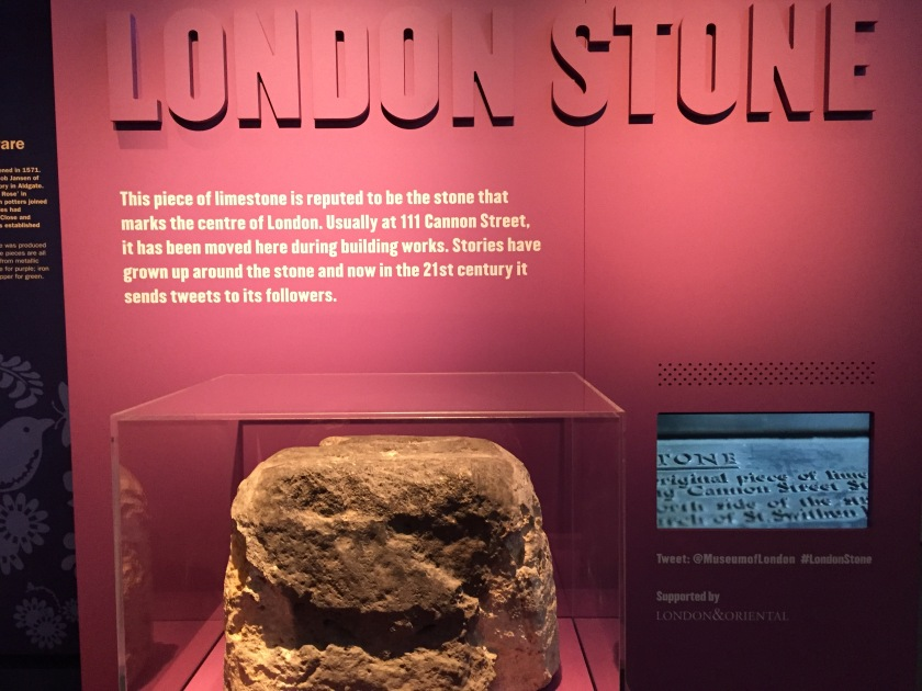A large piece of limestone in front of a large dark pink panel with large bold white text, describing it as the London Stone that is reputed to mark the centre of London at 111 Cannon Street.