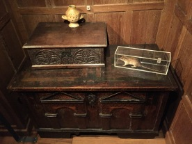 On top of a large wooden cabinet is a small ornate wooden box, on top of which is a small urn with holes in the side and handles on each side. Also on top of the cabinet, on the right side, is a rat in a glass case.
