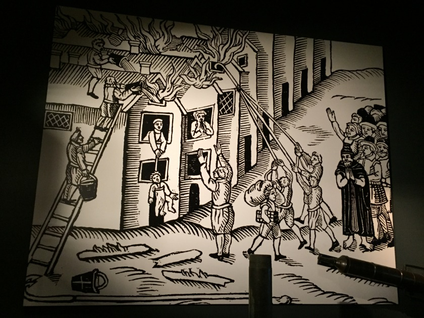Black and white cartoon depicting the Great Fire Of London. A crowd watches as people with buckets of water climb a ladder to fight the fire on the roof of a house, while a person inside the house has a rope tied around their child's chest, and is attempting to lower them to safety through the window.