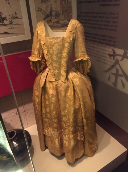 A long, full golden dress with flowery patterning and ruffled edging.