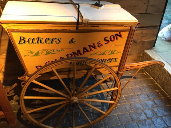 A yellow Victorian bakers and confectioners wagon, with 1 large wheel on each side.
