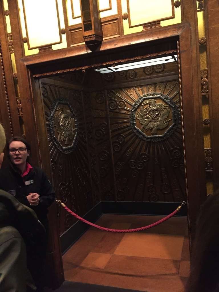 A female member of museum staff giving a talk in front of a big, open lift from Selfridges. The walls of the lift are ornately decorated, the notable feature being a large octagon shape containing 3 golden birds flying in a circular formation.