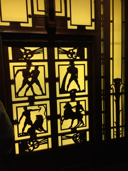 Doors of the Selfridges lifts. The doors have black squares against a yellow background, and inside the squares are black silhouette of people doing things like fighting, taming a lion and riding horseback.