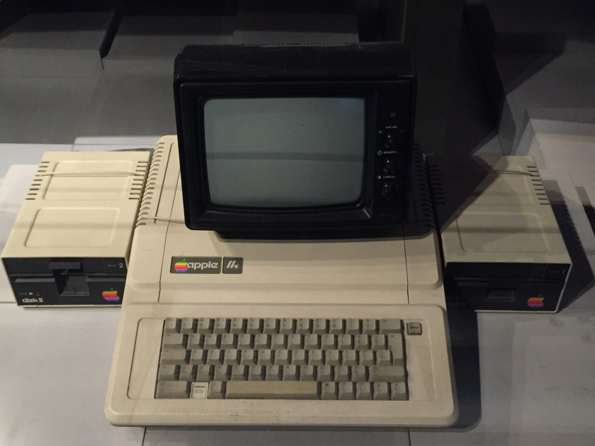 An Apple 2E computer, with a keyboard, small bulky monitor and drives for floppy disks.