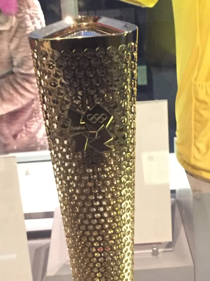 London 2012 Olympic Torch, tall and gold with small round holes all over it, and the 2012 Olympic logo embossed on it.