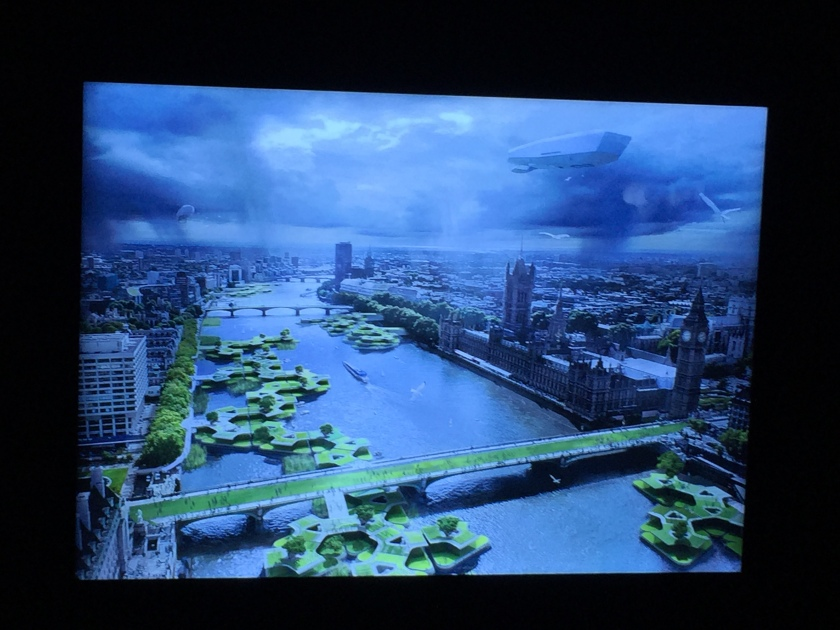 Artist's vision of future London. From the air, we look down the Thames towards Westminster Bridge and the Houses of Parliament. The bridge is covered in green and along the river are lots of round green gardens on the water., with steps leading down to them from the bridge.