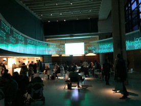 Museum café, with a computer screen stretching around the curved ceiling above, green in colour and filled with lots of random words, including trending, stop, Kent, board, second city derby, league, topic and Saturday.