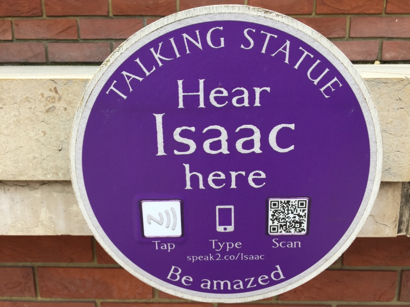 Circular blue plaque with white text that says Talking Statue, Hear Isaac here, Be Amazed. 3 icons invite the reader to either tap the plaque with a phone that can read the chip inside it, or scan a QR code, or manually type in a short web address - speak2.co/Isaac