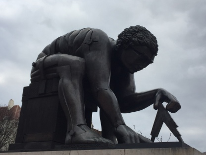 Statue of Isaac Newton kneeling down on one knee, and with one hand flat on the floor, as he measures something on the ground using a triangular shaped device in his other hand.