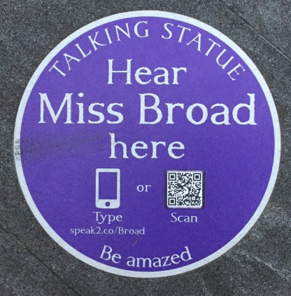 Circular blue plaque with white text that says Talking Statue, Hear Miss Broad here, Be Amazed. 2 icons invite the reader to either scan a QR code or manually type in a short web address - speak2.co/Broad