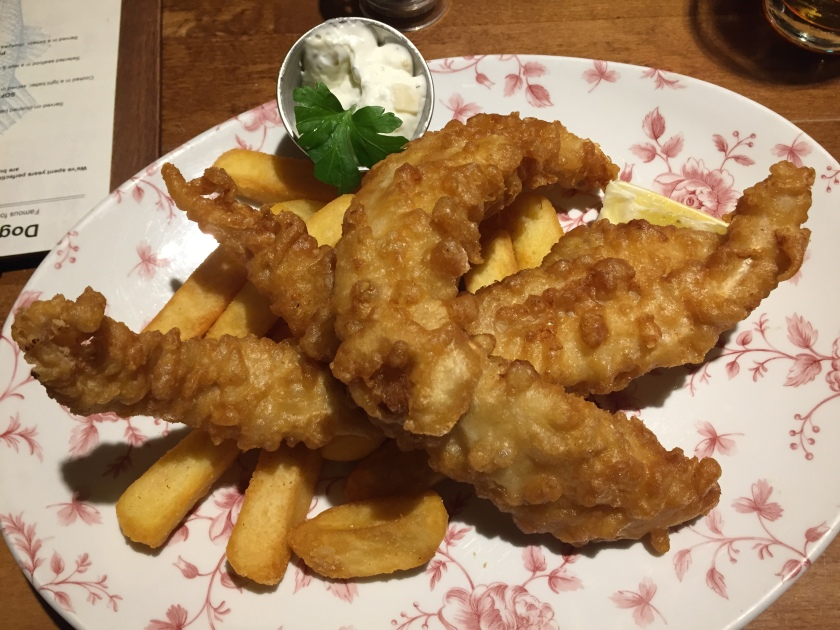 3 long pieces of battered cod on top of chunky chips, with a small pot of tartare sauce.