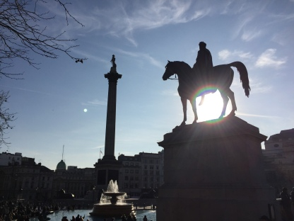 Trafalgar Square. Nearest to the camera, on the right, is a square plinth, on top of which is a statue of a man on a horse, with the sun shining through the space between the horse's front and back legs. To the left, further away, is Nelson's column towering over a circular fountain.