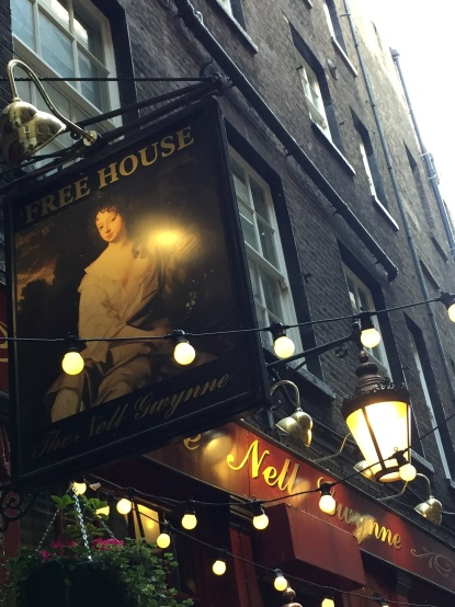 Exterior of Nell Gwynne's Tavern, including a sign featuring a portrait of Nell below the words Free House. Strings of lights also cross the front of the pub, and an old fashioned lantern style light hangs out from behind the portrait sign.