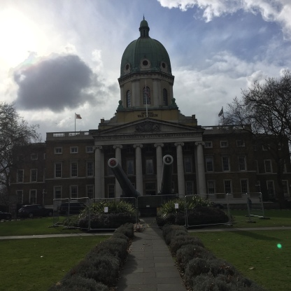 Exterior of the Imperial War Museum building, with 2 large cannons pointing towards the camera from the centre of the circular garden area.