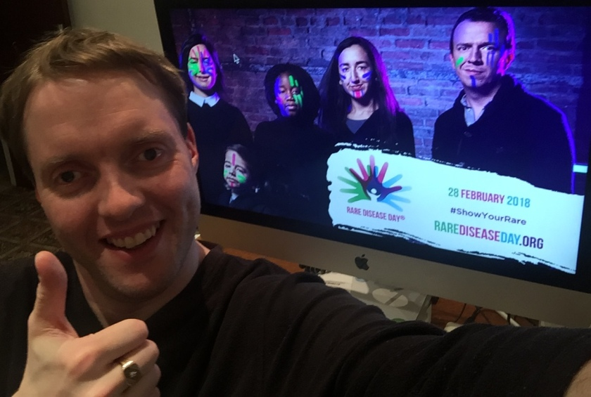 Glen smiling and giving a thumbs up, in front of the Rare Disease Day promotional image on his computer. The promo image shows 5 people wearing luminous face paint, and a banner in the corner says Rare Disease Day, 28 February 2018, Show Your Rare, RareDiseaseDay.org.