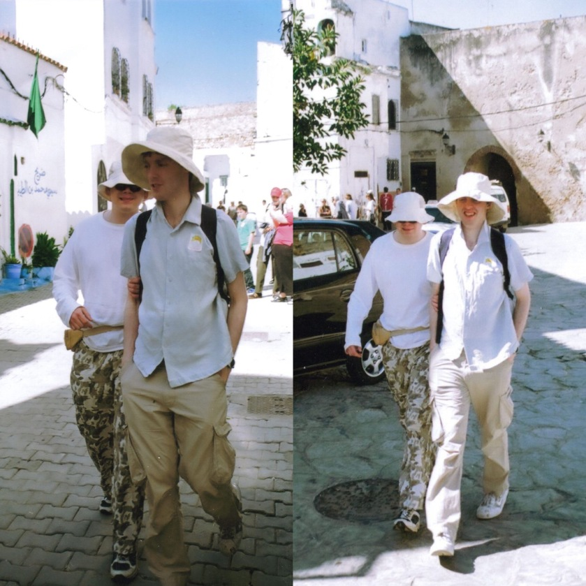 2 photos side by side of me and my male friend walking through the streets of Tangier, Morocco, in the bright sunshine, with tall white buildings in the background. We're wearing white sunhats and white tops. I'm wearing cream cargo trousers, while my friend is wearing trousers with an army camouflage pattern.