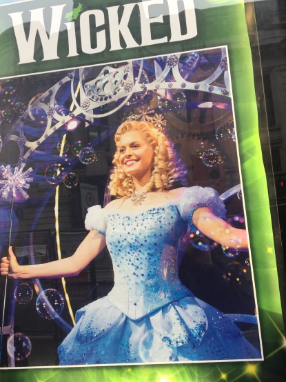 Poster showing the blonde, smiling Good Witch Glinda in her big blue dress, covered in sequins, and holding a wand with a large spiky silvery head on it.