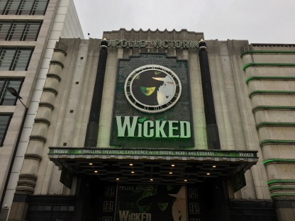 """Wicked sign above the Apollo Victoria Theatre, with Elphaba, the green coloured Wicked Witch of the West, in the middle of a clock face, above the show's title in large letters. Along the front of the narrow canopy above the theatre entrance is white text on a green background, which reads: """"Wicked - A thrilling theatrical experience with brains, heart and courage."""""""