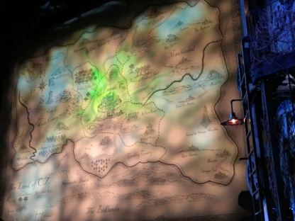 Map of The Land Of Oz on the stage curtain, with The Emerald City in the centre, Gillikin Country to the north, Munchkinland to the east, Quadling Country to the south, and Winkie Country to the west, along with Impassable Desert and Badlands across the southermost section of the map.