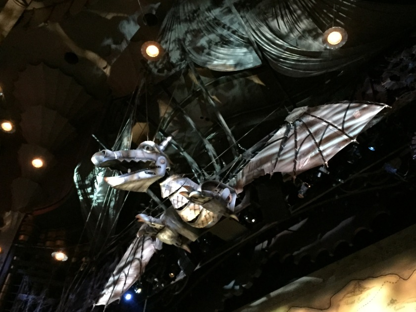 Large silver dragon above the stage, its wings spanning the entire width of the space, and its large head with open mouth looking straight ahead over the audience.