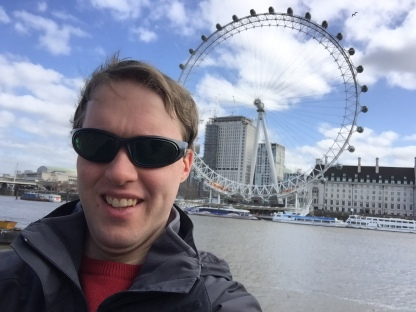 Selfie of Glen smiling and wearing sunglasses, with the London Eye behind him on the opposite side of the River Thames.