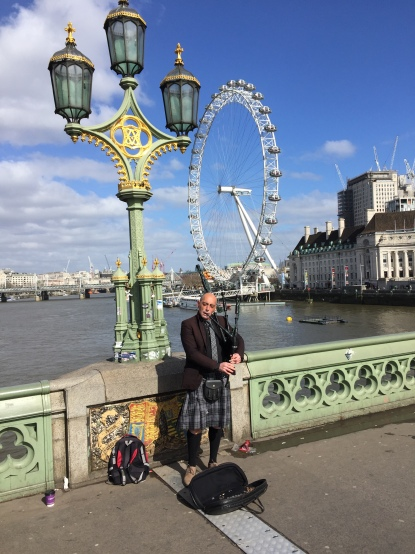Bagpiper standing and playing by an ornate lamppost on Westminster Bridge, with the London Eye visible in the background.