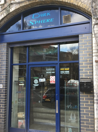 Dark Sphere gaming shop entrance, with doorways and windows surrounding by blue frames, and the words Dark Sphere in a lighter blue on the curved window above the door.