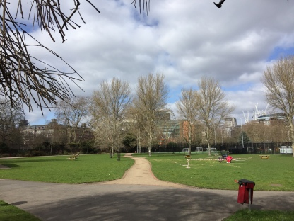 Pathway with green grass on each side, and trees in the distance, in Archbishop's Park