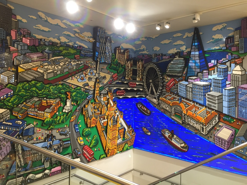 Large colourful Lego artwork of an aerial view of London, with the Thames in the centre, and iconic sights including Buckingham Palace, Trafalgar Square, Big Ben, The Houses of Parliament, Tower Bridge, The London Eye & The Shard.