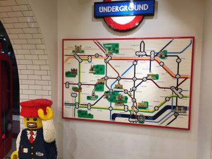 Lego version of the central section of the London Underground Map, with a Lego Underground roundel sign above it, and a Lego model of a smiling train guard on the floor in front of it.