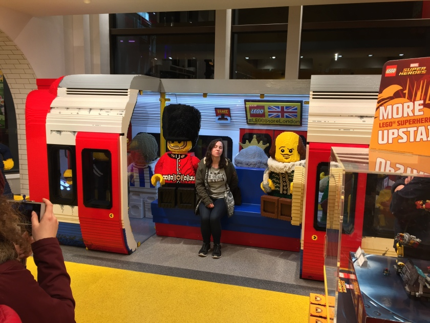 Large Lego model of a London Underground train carriage with its doors open. A Lego guard and a Lego Shakespeare are sitting inside, and a real-life woman is sitting in between them to have her photo taken.