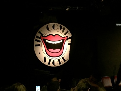 Logo for The Comedy Store - A large white circle with a cartoon of a laughing mouth in the centre, with black text around the edge of the circle that says The Comedy Store.