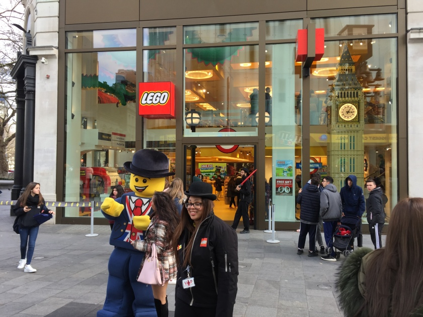 Outside the Lego Store, someone dressed as a lifesize yellow Lego Man, in a blue suit, Union Jack shirt and black bowler hat, poses with a lady member of the public for a photo. Next to them is a smiling female member of staff, wearing a black jacket with the Lego logo and black bowler hat.