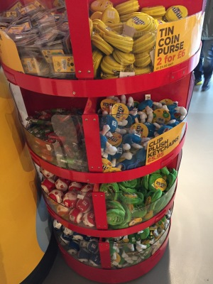 Various items of M&M's branded merchandise, including guitar picks, tin coin purses and plush keychains