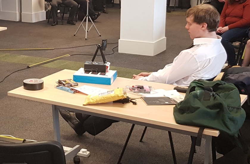 Photo of me sitting and watching one of the presentations. On the table next to me is my iPhone on a small tripod, standing on top of a couple of small boxes to give it the right height.