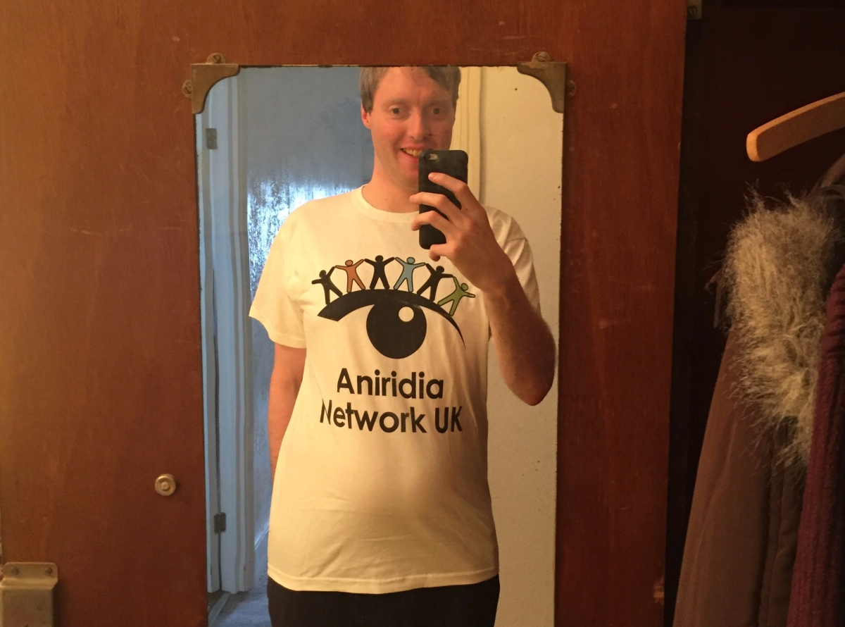 Selfie of me taken in a full length mirror at home, wearing a white t-shirt with the Aniridia Network logo in the middle. It is a silhouette of an eyebrow over a pupil with a glint of light in it. Standing across the top of the brow are 6 differently coloured figures, like gingerbread men, holding hands.