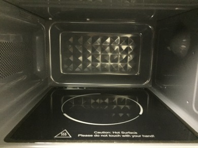 Inside of the Russell Hobbs microwave, showing a flat black base with a white circle on it instead of a turntable. White text near the door warns not to touch the hot surface.