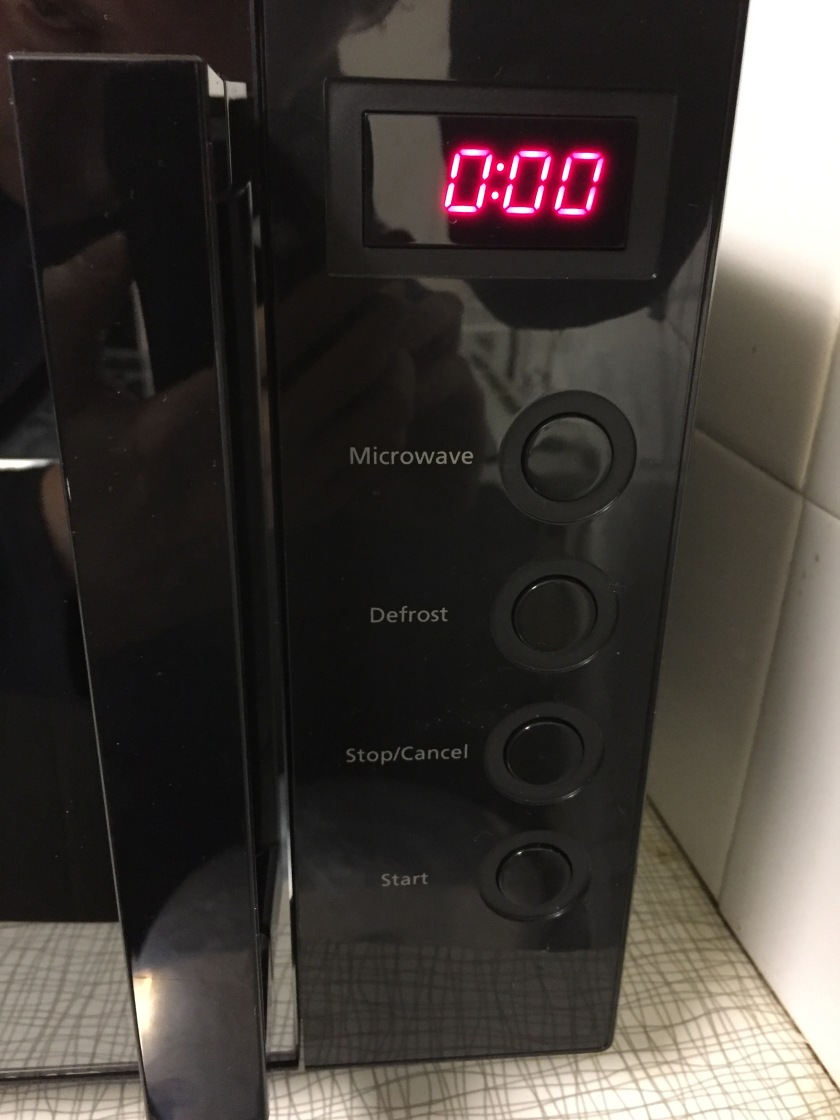 The right side of the black coloured microwave. A screen at the top shows the time in clear red figures. Below this are 4 large round buttons, each with white text to the left of them - for Microwave, Defrost, Stop and Start respectively.