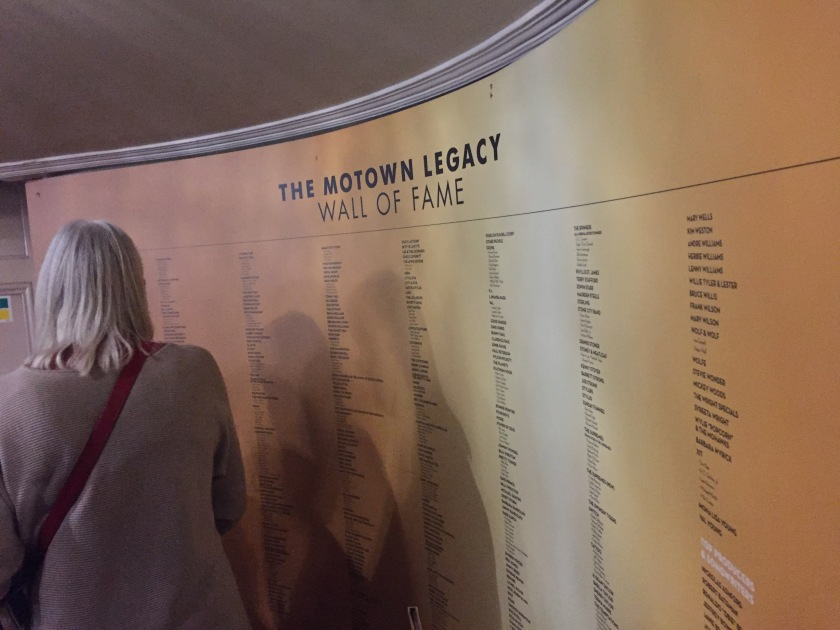 The Motown Legacy Wall Of Fame, a huge gold coloured poster along a curved wall, listing hundreds of names of Motown artists.